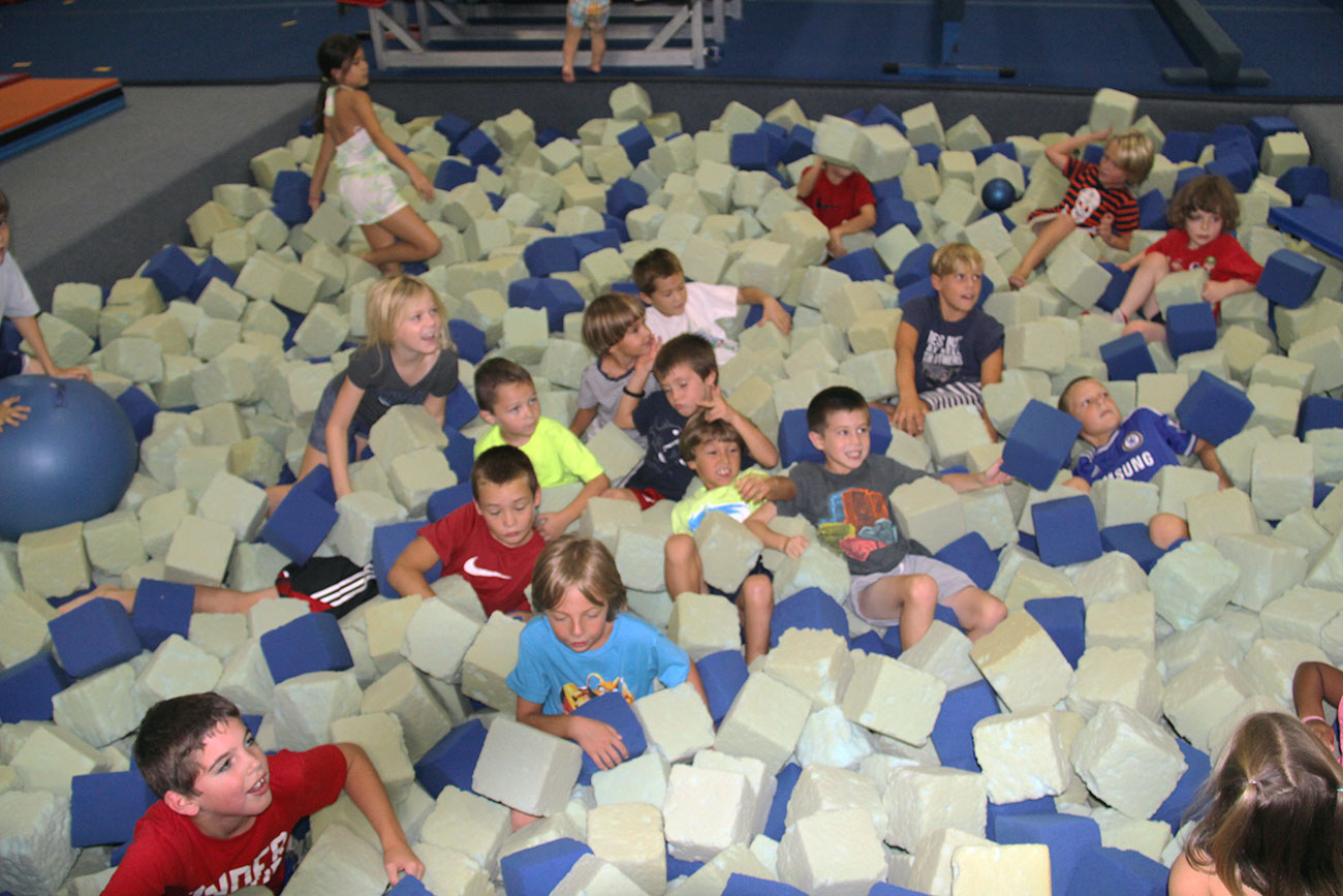 A group of campers plays in the foam pit