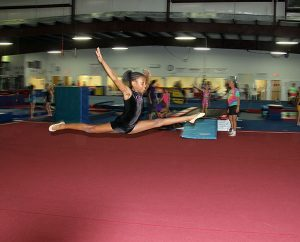 A student does a leap during a practice routine