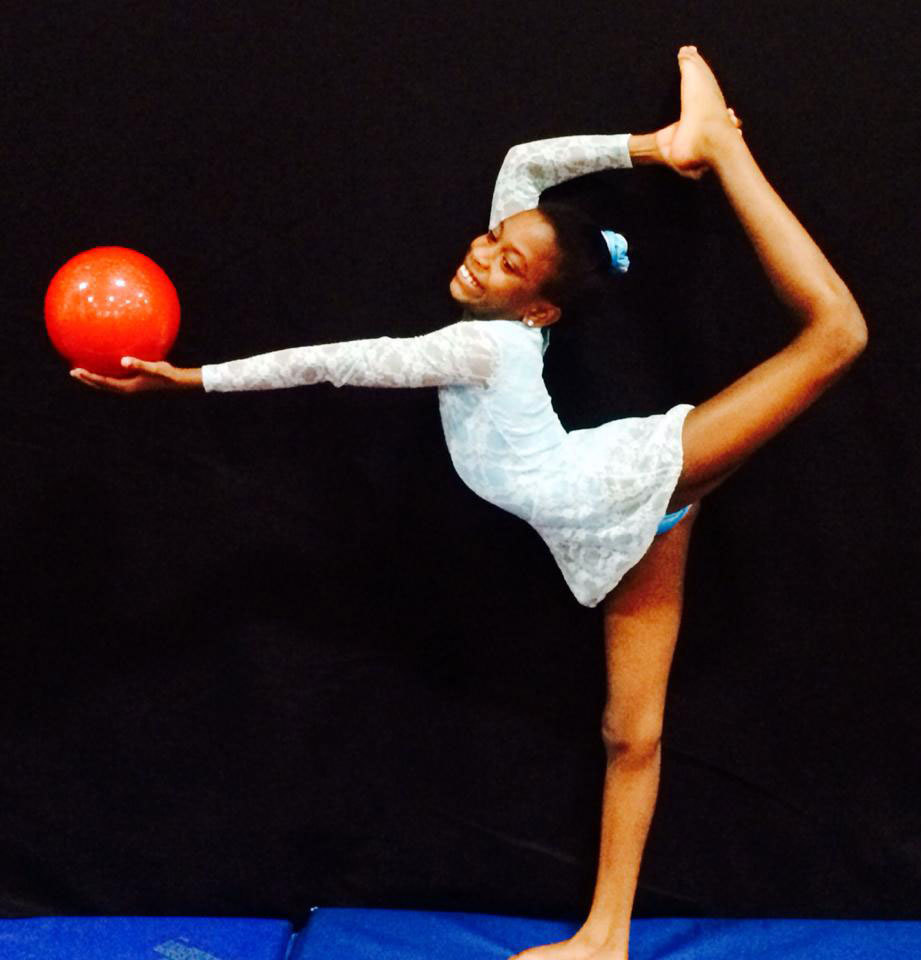 A girl practices ryhthmic gymnastics with a ball