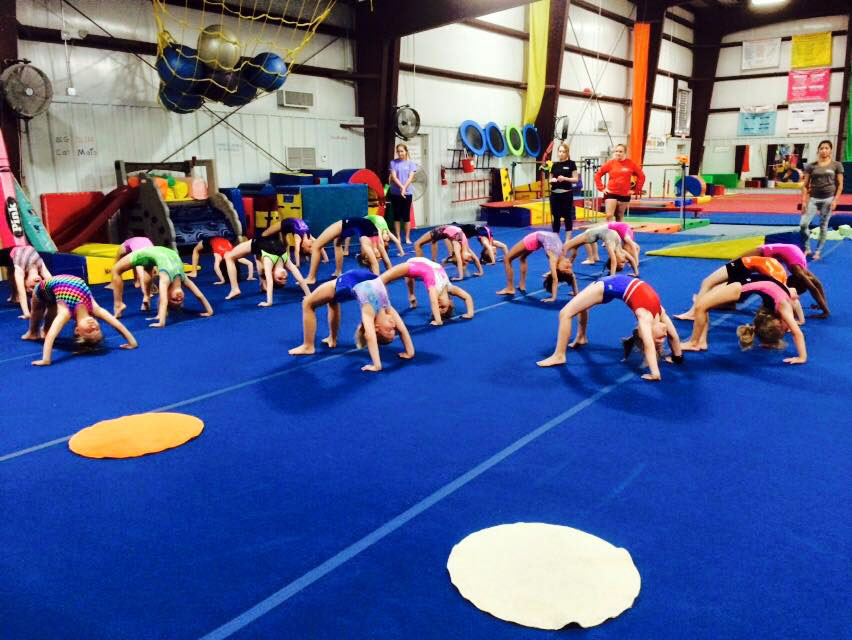 Several school-aged gymnasts do backbends under the watchful eye of our instructors