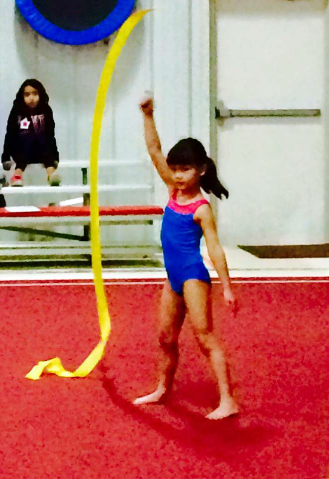 A young gymnast works with a ribbon