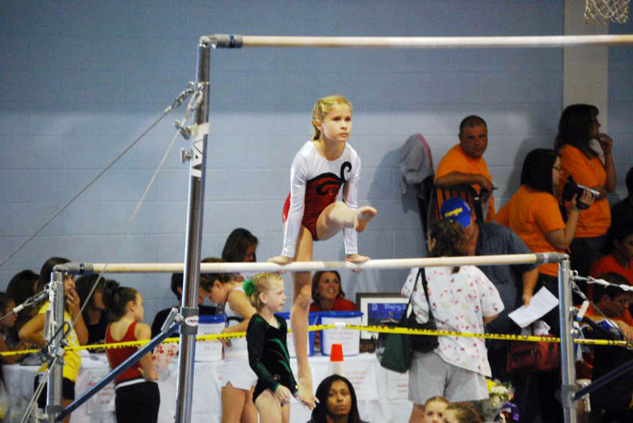 A girl competes on the uneven bars