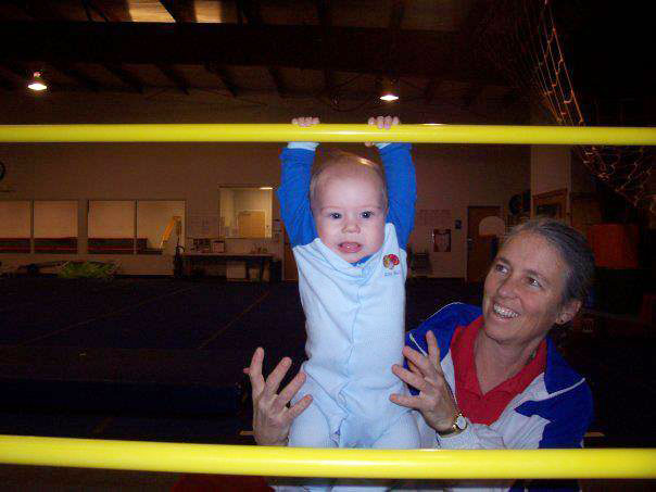 Michele helps am infant play on the uneven bars